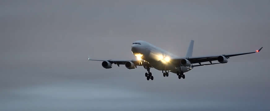 Airliner on final approach with landing lights lit along with red and green position lights