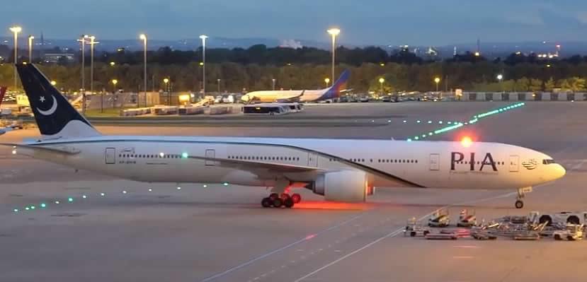 PIA Boeing 777-300 at the gate at night